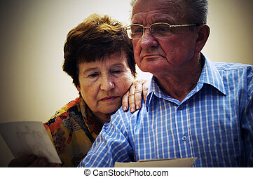 Senior couple looking at old photographs. Reminisce about...
