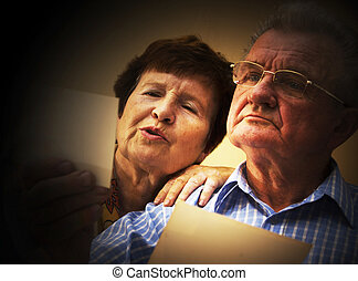 Senior couple looking at old photographs.