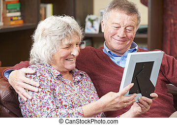 Senior Couple Looking At Photograph In Frame Together