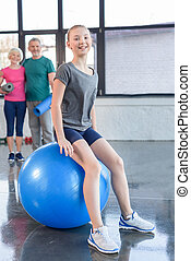 Senior couple looking at smiling girl training on fitness ball in gym