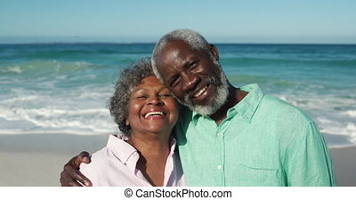 Senior couple looking at the camera at the beach