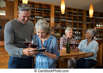 Senior couple looking their photos on mobile phone