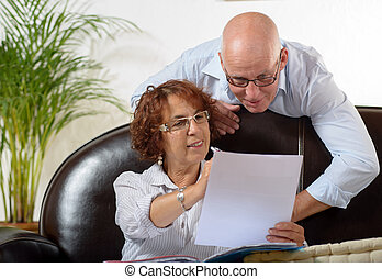 Senior couple looks at a Document