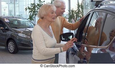 Senior couple looks inside the car at the dealership
