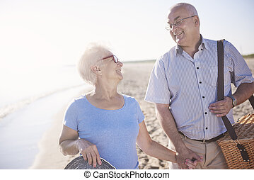 Senior couple loving picnics on the beach