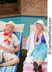 Senior couple lying down beside the