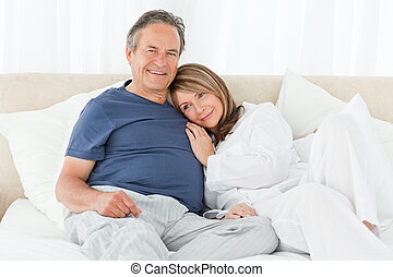 Senior couple lying down on their bed