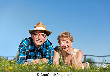 Senior couple lying on the summer field in green grass