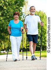senior couple making nordic walking in the park