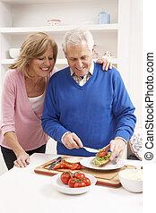 Senior Couple Making Sandwich In Kitchen