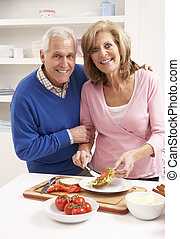 Senior Couple Making Sandwich In Kitchen