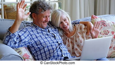 Senior couple making video call on laptop on sofa 4k - Happy...