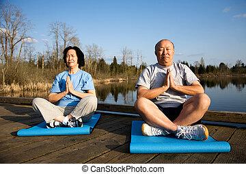 Senior couple meditating - A shot of a senior asian couple...