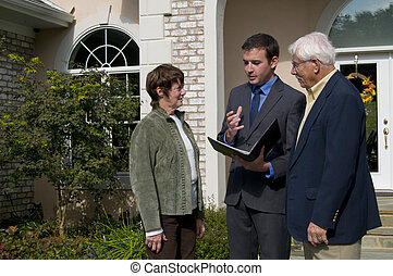 senior couple meeting with realtor - realtor showing a home...