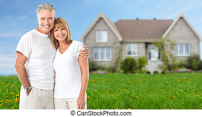 Senior couple near new home. Real estate background.