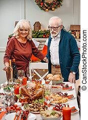 senior couple next to christmas table