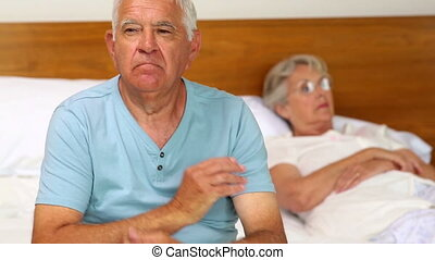 Senior couple not speaking after an argument on bed at home...