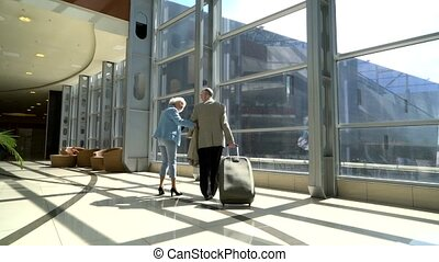 Senior couple of tourists walking with suitcase in airport...