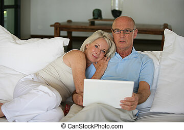 Senior couple on a sofa with laptop computer