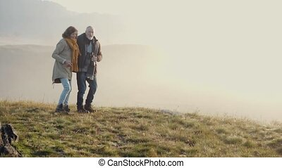 Senior couple on a walk in an autumn nature. - Active senior...