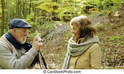Senior couple on a walk in autumn forest. - Active senior...