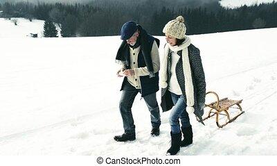 Senior couple on a walk pulling sledge, winter day.
