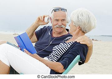 senior couple on beach reading book and listening to headphones