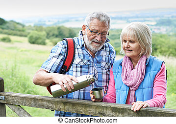 Senior Couple On Hike Having Hot Drink