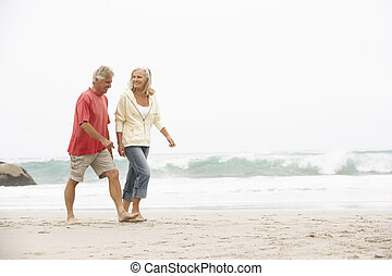 Senior Couple On Holiday Running Along Winter Beach