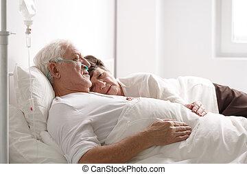 Senior couple on hospital bed