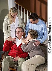 Senior couple on sofa at home with adult children