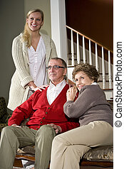 Senior couple on sofa at home with adult daughter - Senior...