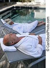 Senior couple on sun loungers by a pool