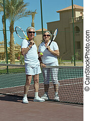Senior couple on tennis court