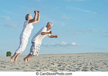 Senior couple on vacation - Amusing senior couple jumping...
