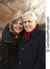 Senior Couple On Winter Walk Through Frosty Landscape