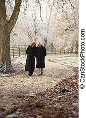 Senior Couple On Winter Walk Through Frosty Landscape