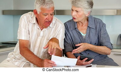 Senior couple organizing their bills at home in the kitchen