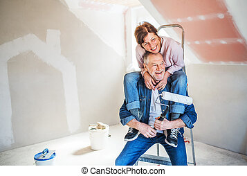 Senior couple painting walls in new home, having fun....