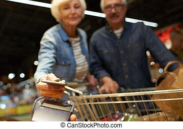 Senior Couple Paying with Mobile Phone - Portrait of senior...