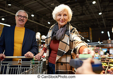 Senior Couple Paying with Phone - Waist up portrait of...