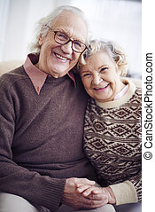 Senior couple - Cheerful senior couple in sweaters looking...