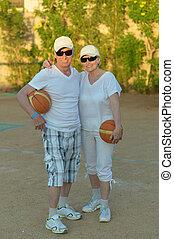 Senior couple playing basketball