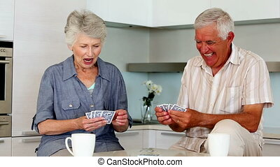 Senior couple playing cards at the