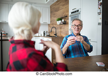 Senior couple playing cards together in kitchen