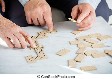 Senior Couple Playing Dominoes At Table