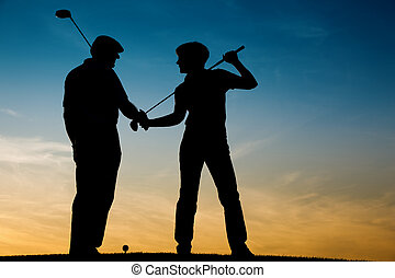 Senior couple playing Golf at sunse