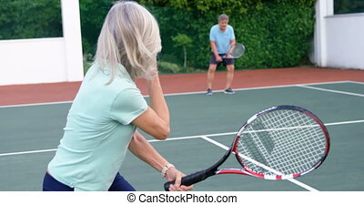 Senior couple playing tennis in tennis court 4k -...