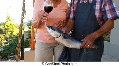 Senior couple preparing fish on barbecue 4k