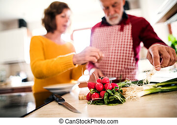Senior couple preparing food in the kitchen.